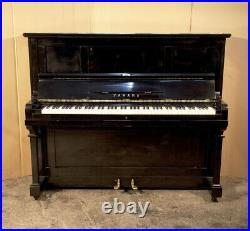 A 1961, Yamaha U2 upright piano with a black case and brass fittings