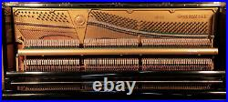 A 1962, Yamaha U2 upright piano with a black case and brass fittings