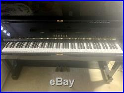 A 1981, Yamaha U1 upright piano with a black case in Excellent condition