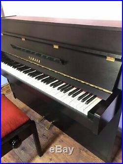 A 1986, Yamaha LU 101 upright piano with a black case