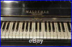 A Waldemar upright piano with a black case, inlaid with doves in a maple tree