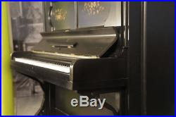 An 1886 Steinway upright piano with a satin, black case and floral inlaid panels